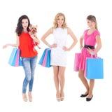 有在白色隔绝的购物袋的三个美丽的女孩 免版税库存照片