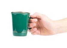 有在白色隔绝的绿色茶杯的手 免版税库存照片