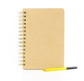 有在白色backgr隔绝的黄色铅笔的包装纸笔记本 免版税库存图片