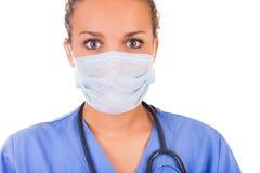 有在白色backgro和听诊器的年轻医生隔绝的面具 免版税库存图片