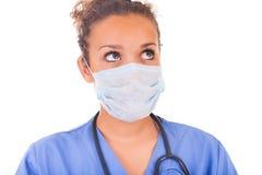 有在白色backgro和听诊器的年轻医生隔绝的面具 免版税库存照片