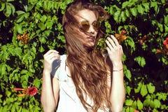 有在站立在爬行物树篱的被反映的太阳镜的风吹的长的栗子头发的Beautifull妇女 免版税库存图片