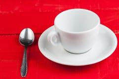 有在红色背景隔绝的金属匙子的加奶咖啡杯子 免版税库存图片