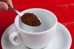 有在红色背景隔绝的金属匙子的加奶咖啡杯子 免版税库存照片