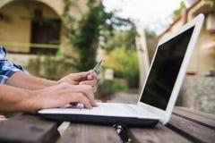 有在网上买的信用卡和的膝上型计算机的手 库存照片