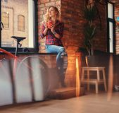 有在羊毛衬衣和牛仔裤穿戴的长的卷发的沉思肉欲的白肤金发的行家妇女拿着一个杯子早晨 图库摄影