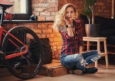 有在羊毛衬衣和牛仔裤穿戴的长的卷发的肉欲的白肤金发的行家女孩拿着一个智能手机坐a 库存图片