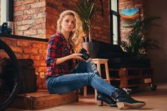 有在羊毛衬衣和牛仔裤穿戴的长的卷发的肉欲的白肤金发的行家女孩拿着一台照相机坐木 图库摄影