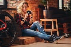 有在羊毛衬衣和牛仔裤穿戴的长的卷发的肉欲的白肤金发的行家女孩拿着一台照相机坐木 免版税库存照片