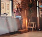 有在羊毛衬衣和牛仔裤穿戴的长的卷发的肉欲的白肤金发的行家女孩拿着一台照相机坐窗口 库存照片