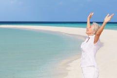 有在美丽的海滩伸出的胳膊的资深妇女 库存图片