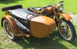 有在草停放的边车的葡萄酒摩托车 免版税库存照片