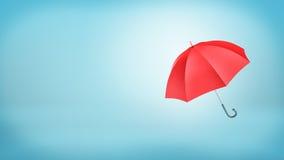 有在蓝色背景垂直安置的把柄的一把开放经典红色伞 免版税库存照片