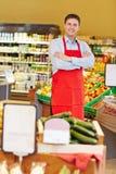 有在超级市场横渡的胳膊的推销员 免版税库存图片