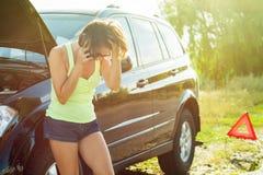 有在路发生故障的一辆黑汽车的妇女 库存图片