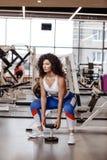 有在运动服穿戴的黑暗的卷发的俏丽的亭亭玉立的女孩做着与重的哑铃的蹲坐在现代健身房 免版税库存照片