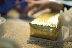 有在金黄枕头安置的手表的手得到修指甲 库存图片