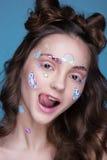 有在面孔胶合的滑稽的专业构成和emoji贴纸的美丽的时尚女孩 免版税图库摄影