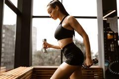 有在黑体育上面和短裤穿戴的棕色头发的美丽的运动女孩举行在健身房的哑铃 免版税库存照片
