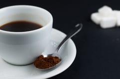 有在黑背景隔绝的糖立方体的加奶咖啡杯子 库存图片