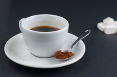 有在黑背景隔绝的糖立方体的加奶咖啡杯子 免版税库存照片