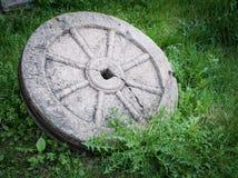 有在绿草隔绝的生锈的金属外缘的石花岗岩轮子 免版税库存图片