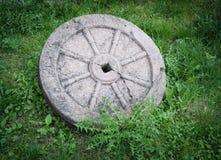 有在绿草隔绝的生锈的金属外缘的石花岗岩轮子 库存图片
