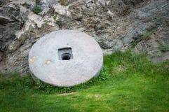 有在绿草隔绝的生锈的金属外缘的石花岗岩轮子 库存照片