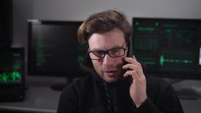 有在黑衣裳穿戴的镜片的人在屋子里坐并且在电话里说 年轻黑客是 股票录像