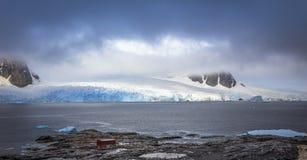 有在c和冰川的岩石海岸线全景掩藏的山 图库摄影
