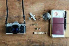 有地图、护照和照相机的笔记本在木背景 图库摄影