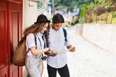 有地图和照相机的两个年轻游人在老镇 免版税图库摄影