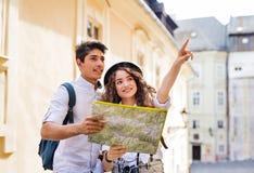 有地图和照相机的两个年轻游人在老镇 库存照片