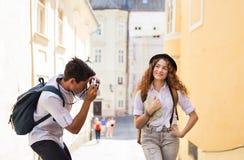 有地图和照相机的两个年轻游人 免版税库存图片