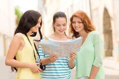 有地图和照相机的微笑的十几岁的女孩 库存照片