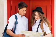 有地图的两个年轻游人在老镇 库存照片