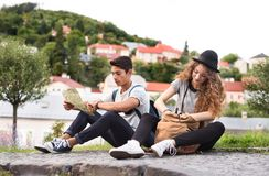 有地图的两个年轻游人在老镇 库存图片