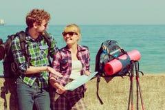 有地图的夫妇背包徒步旅行者由海边 免版税库存图片
