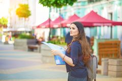 有地图的女孩游人在手中在城市街道旅行指南,旅游业在欧洲 免版税图库摄影