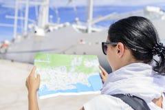 有地图的妇女在海港口的游轮附近 免版税库存照片