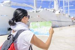 有地图的妇女在海港口的游轮附近 库存照片