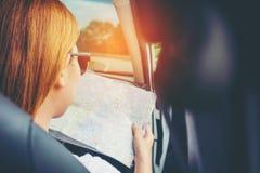 有地图的少妇单独汽车旅客在斜背式的汽车汽车 图库摄影