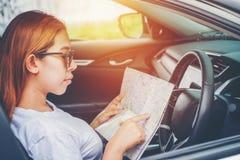 有地图的少妇单独汽车旅客在斜背式的汽车汽车 库存照片