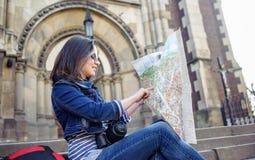 有地图的少妇在老市中心 库存照片