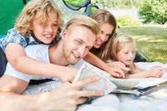有地图的幸福家庭,当野营时 库存照片