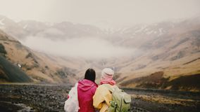 有地图的旅行的妇女走在山的后面观点的两 有背包的游人在冰岛设法发现方式 股票视频