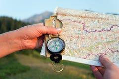 有地图的游人的在Switze山的手和指南针  免版税库存图片
