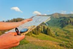 有地图的游人的在Switze山的手和指南针  库存照片