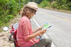 有地图的美丽的少妇在手中和在ro的一辆摩托车 免版税库存照片