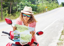 有地图的美丽的少妇在手中和在ro的一辆摩托车 免版税库存图片